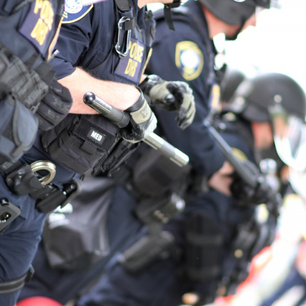 Law enforcement in riot suits during summer combating heat exhaustion and dehydration.